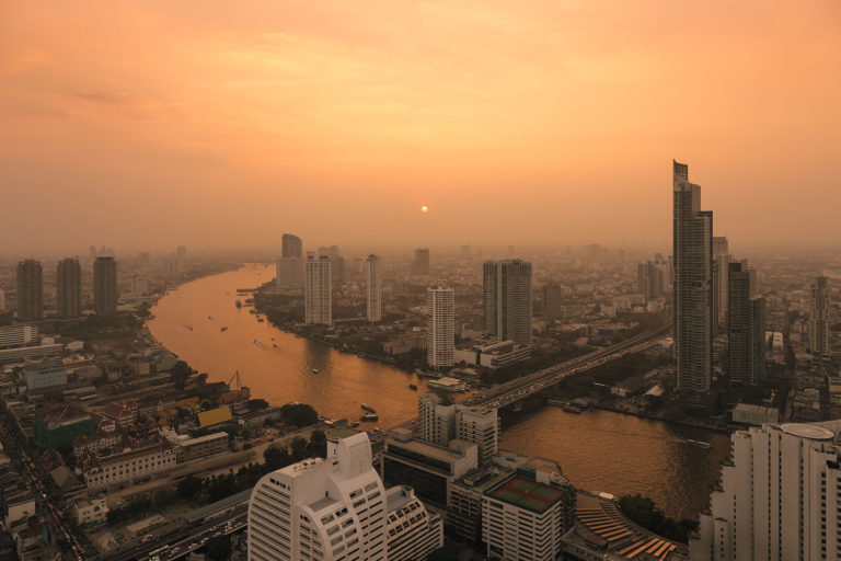 Hazy Sunset over the Chao Phraya River and the Bangkok Skyline (Thailand)