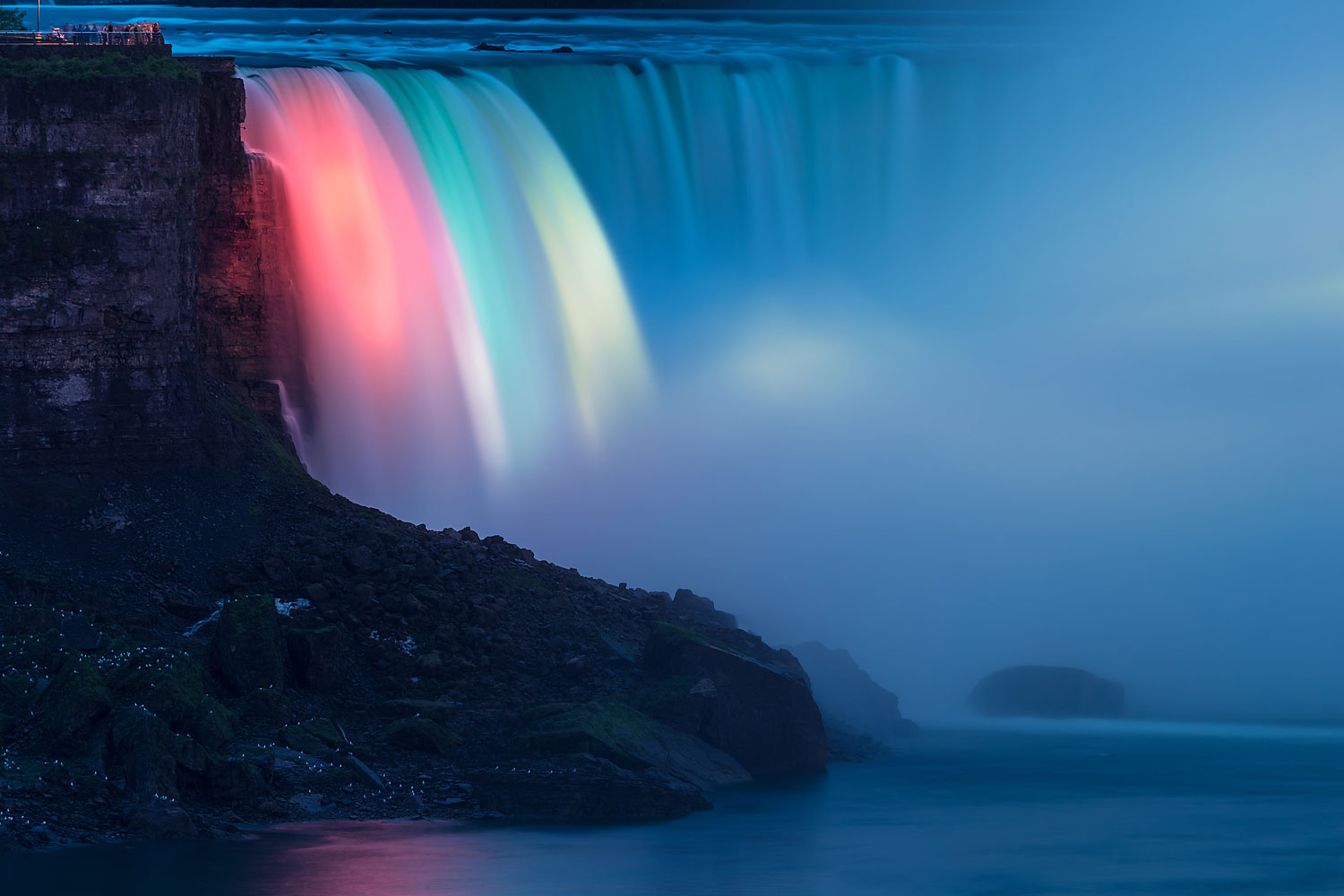 Niagara Falls - Illuminated Horseshoe Falls a.k.a. Canadian Falls as Seen from the Canadian Side in the Evening Every evening colorful lights illuminate the Falls. The rock on the left is Goat Island (United States). The white spots on the rock are birds.