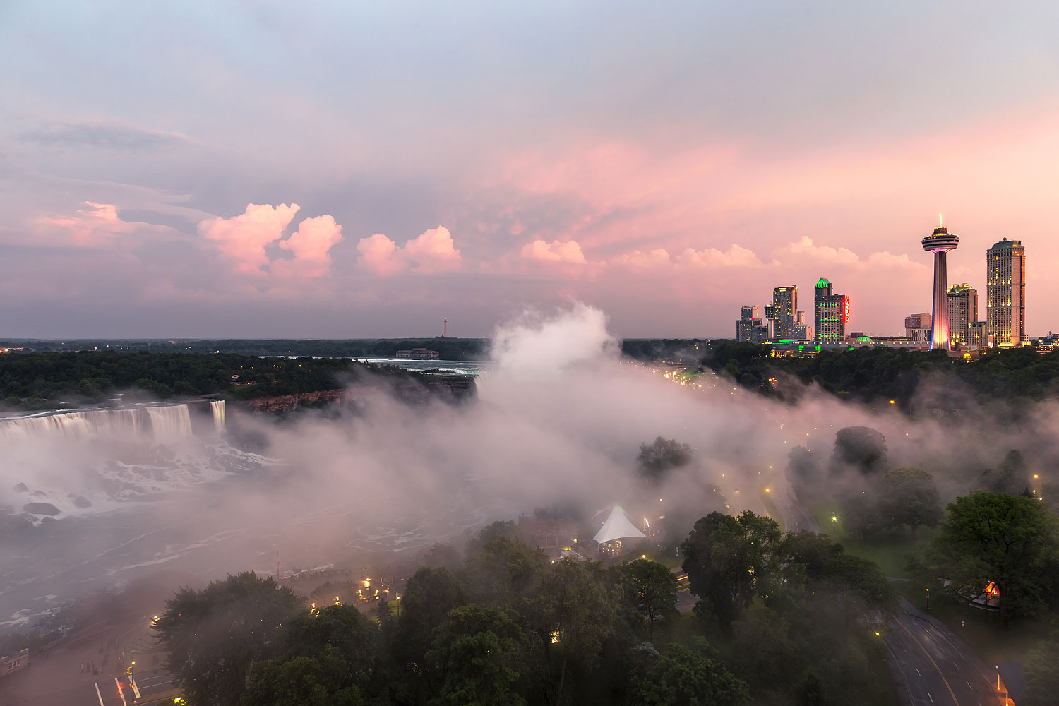 Panorama of Niagara Falls at Twilight, Canada / United States. View from the Canadian side, on left: the American Falls, in the center: the Canadian Falls (a.k.a. Horseshoe Falls), on the right: the skyline of the town Niagara Falls, Ontario.