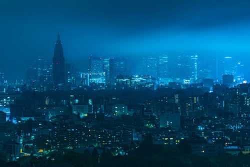 Moonlight gleaming through clouds and thick fog over Shinjuku skyline in Tokyo, Japan