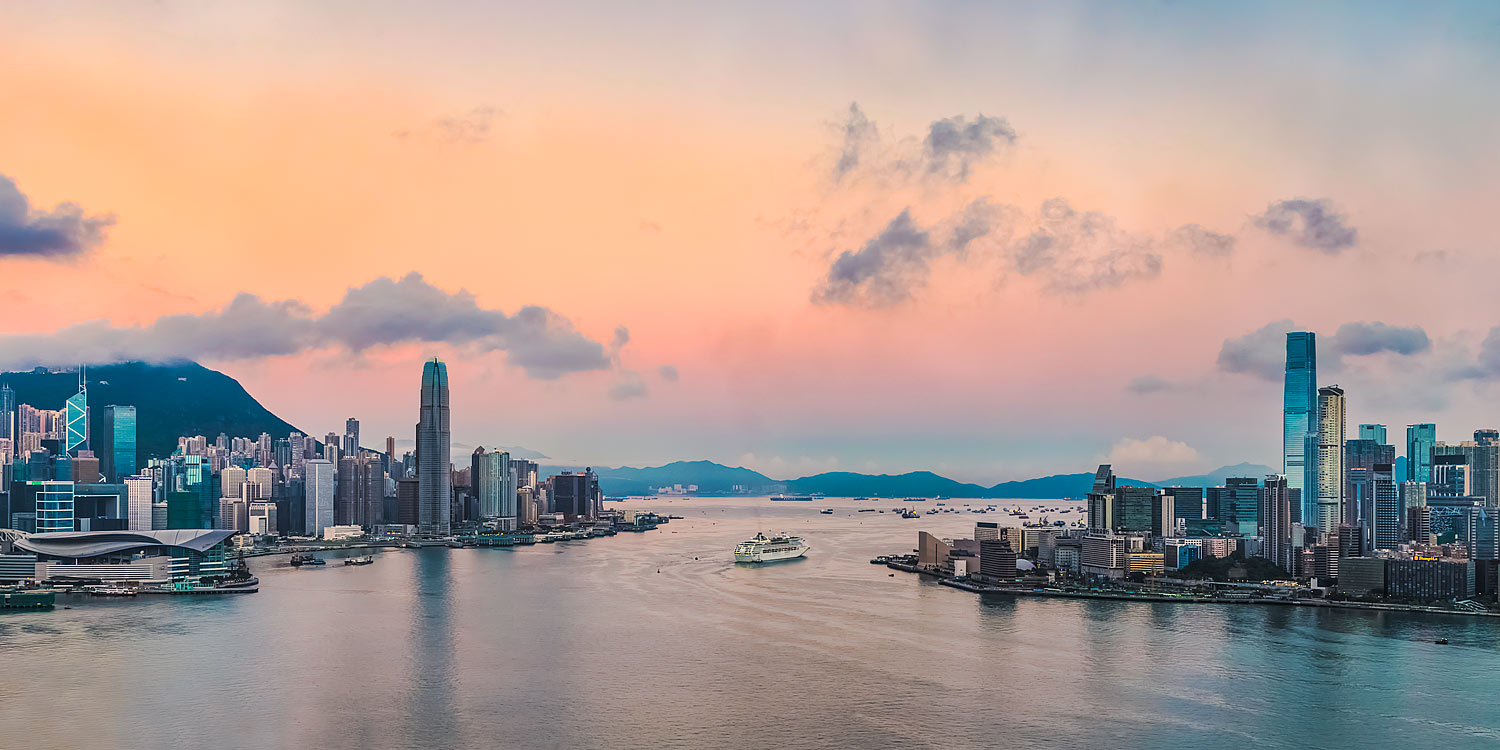 Panorama of Hong Kong at sunrise, with  Hong Kong Island on the left and Kowloon on the right