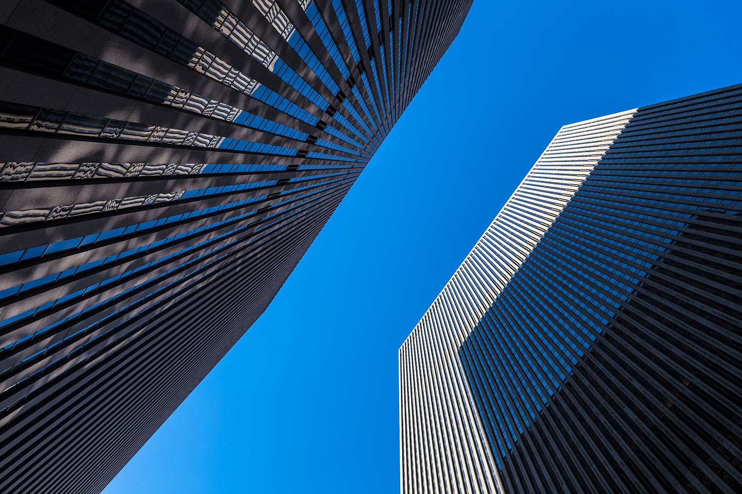 Upward view of two skyscrapers in New York City. One skyscraper casts a shadow onto the other one.