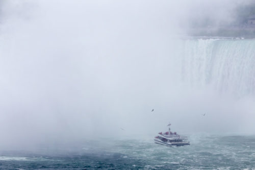 A Boat with Tourists Approaches the Mist Created by the Canadian Falls